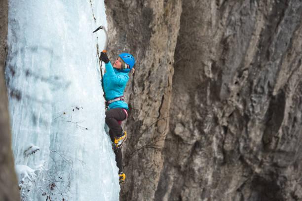 凍った滝を登る若い女性氷 - アイスクライミング ストックフォトと画像