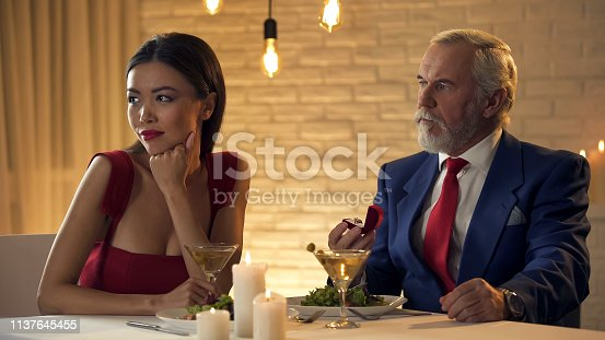 Young woman ignoring old oligarch holding ring present, relationship for money
