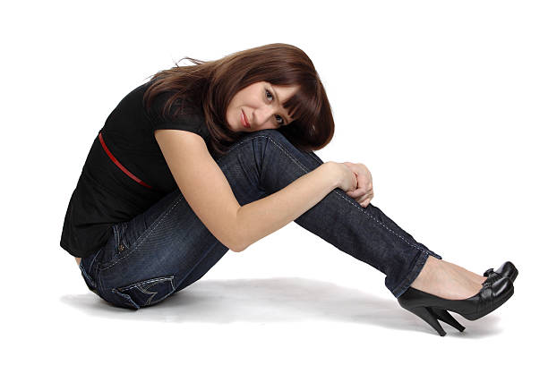 Young woman iis embracing own lap. stock photo