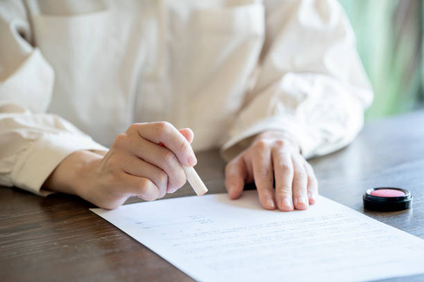 Young woman imprinting documents at desk stock photo
