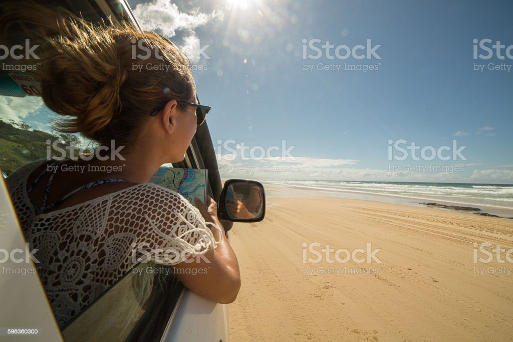 Young woman in 4x4 reads a road map, Fraser Island stock photo