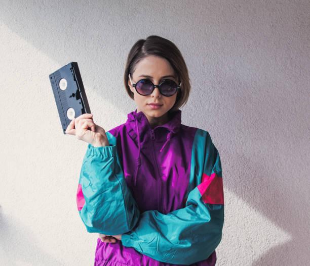 junge frau im 90er-jahre-stil kleidung mit vhs-kassette - 80er outfit stock-fotos und bilder