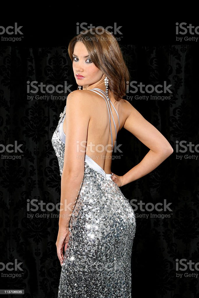 Young woman in a backless silver dress stock photo
