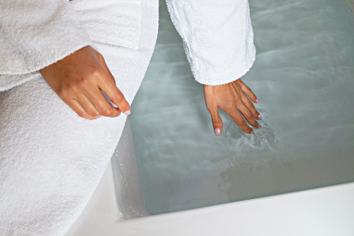 Cropped shot of young woman wearing the white bathrobe touching the water in a filled bathtub. Unrecognizable female testing the temperature of a tub with her fingers. Close up, copy space, background