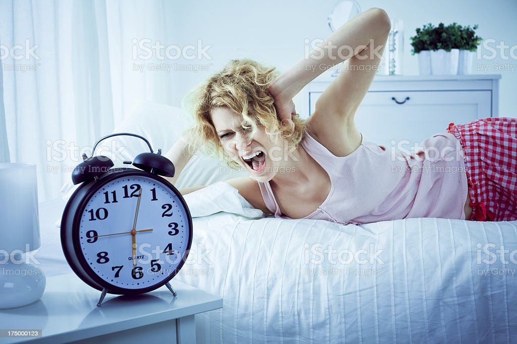 Young woman in a bedroom Young woman lying on her bed in the morning, covering ears with hands and screaming at alarm clock. 25-29 Years Stock Photo