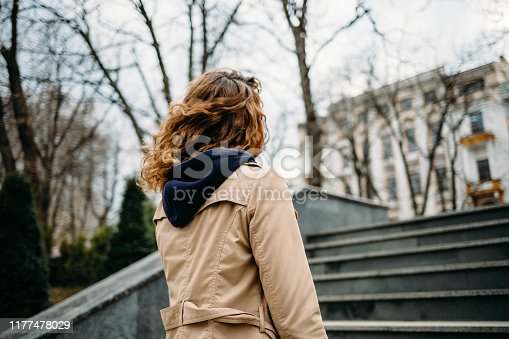 A young woman in a beige coat climbs the stairs in the city