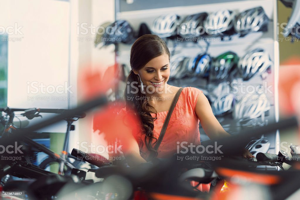 Young woman in a bike store Smiling young woman watching bikes in bike store. 20-24 Years Stock Photo