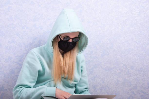 Uma jovem com uma máscara protetora de vírus reutilizável preta, óculos pretos e uma jaqueta encapuzada trabalha em um computador em casa. O conceito de trabalho remoto em casa - foto de acervo