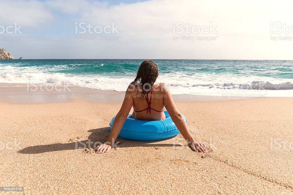 young woman in a blue rubber ring enjoying the beach stock photo