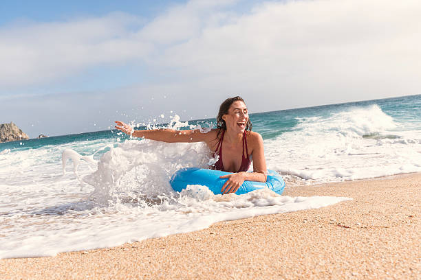 young woman in a blue rubber ring enjoying the beach - rubber ring stock photos and pictures