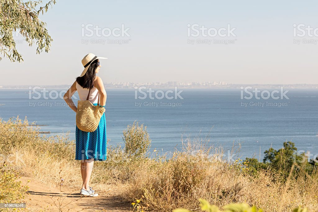 Young woman (brunette) in a blue skirt and hat looks - foto de stock