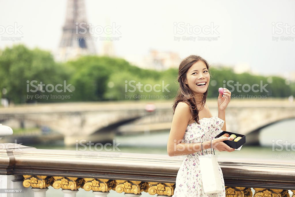A young woman in a bridge in Paris, holding macaroons royalty-free stock photo