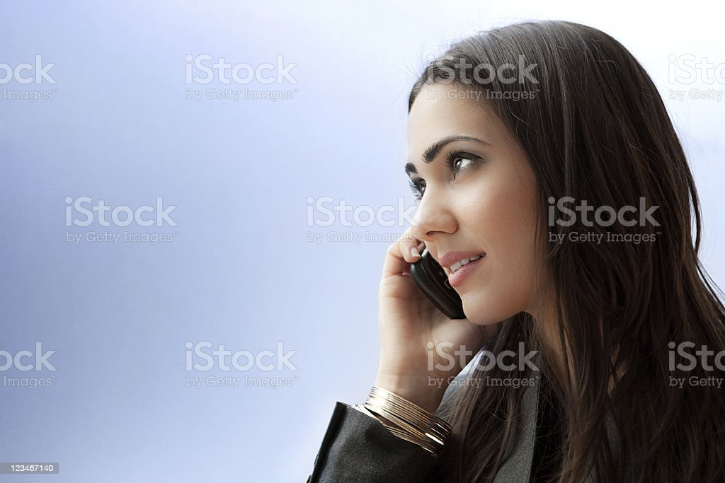A young woman in a business suit talks on her smart phone royalty-free stock photo