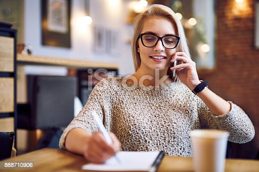 Young woman in a cafe talking on the phone and taking notes