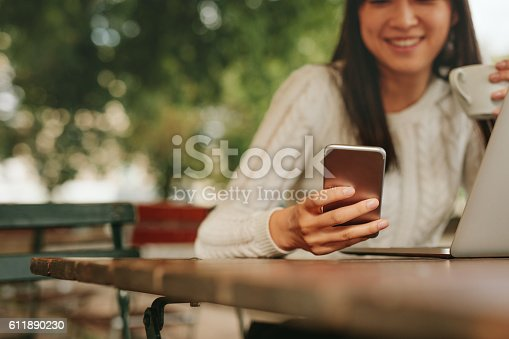 Young woman in a cafe reading a text message from her mobile phone. Chinese female sitting at cafe table with laptop and using smart phone.