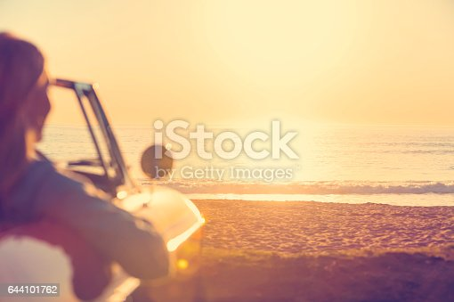 Young woman in a car at the beach. The car is a convertible, with the sunset and ocean backlit in the background. She looks relaxed and happy looking at the waterfront view.