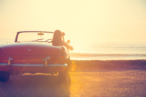 istock Young woman in a car at the beach. 644101764
