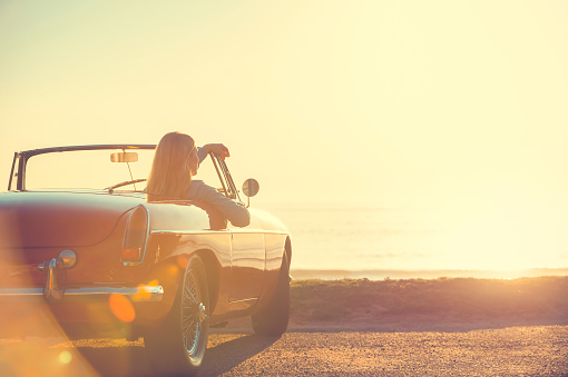 istock Young woman in a car at the beach. 644101772