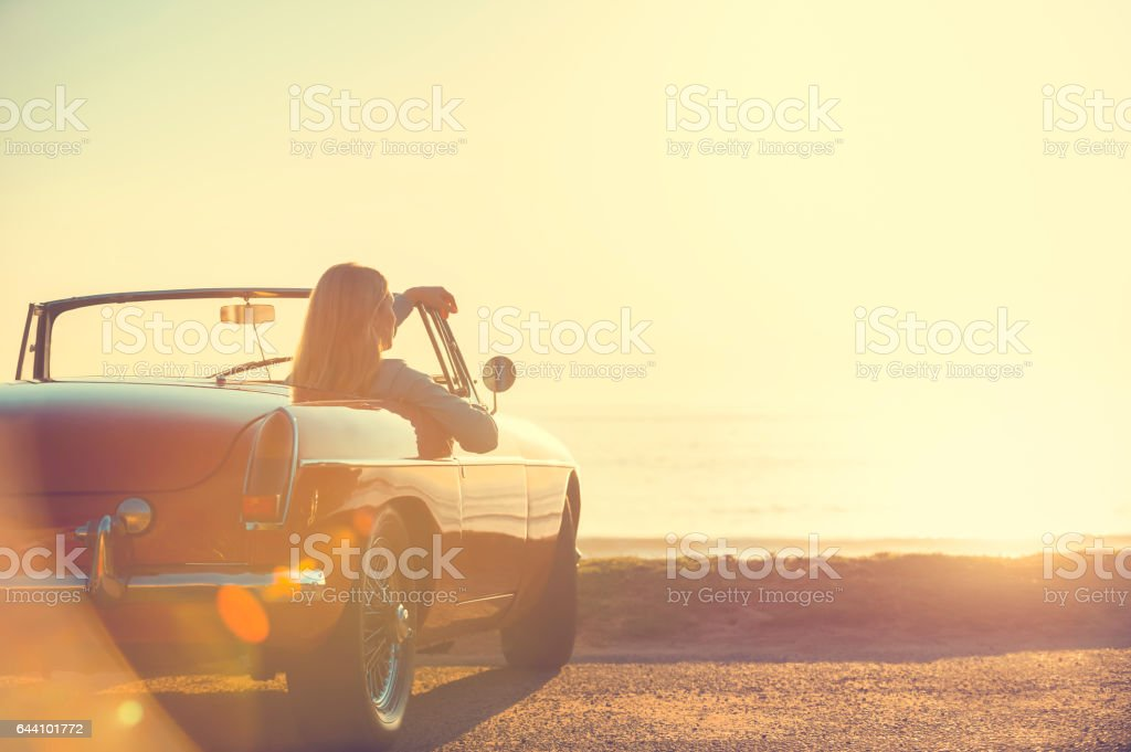 Young woman in a car at the beach. stock photo