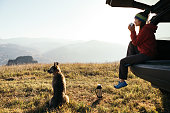 A young woman in a car on a background of mountains sits relaxed and drinks hot tea. A faithful and beloved dog sits nearby. They climbed to the top by car. Autumn. Karachay Cherkessia.