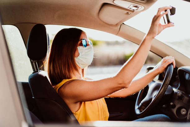young woman in a car wearing protective mask. Summer season. prevention corona virus concept stock photo