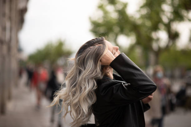 Young woman in a city touching her bleached hair stock photo