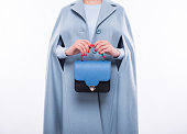 istock Young woman in a coat holding blue-black purse 673822870