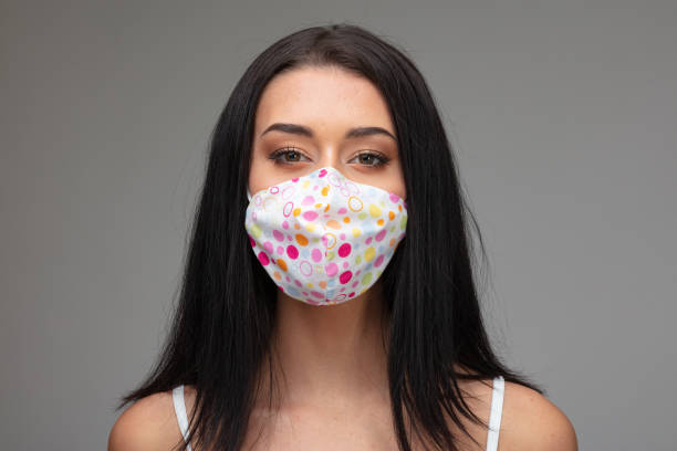 jonge vrouw in een kleurrijk masker van het weefselgezicht - verduisterd gezicht stockfoto's en -beelden