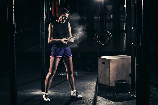 Young woman in a cross training rack stock photo