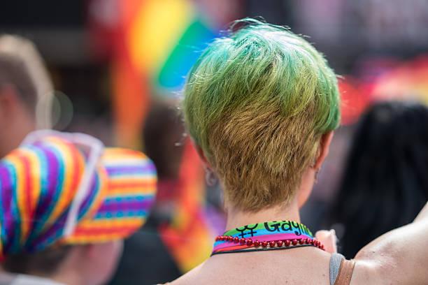 young woman in a crowd celebrating pride parade. - modefarben sommer 2016 stock-fotos und bilder