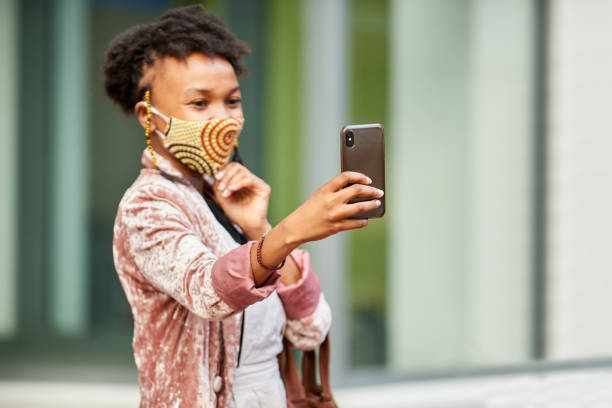 Young woman in a face mask taking a selfie on a city street stock photo