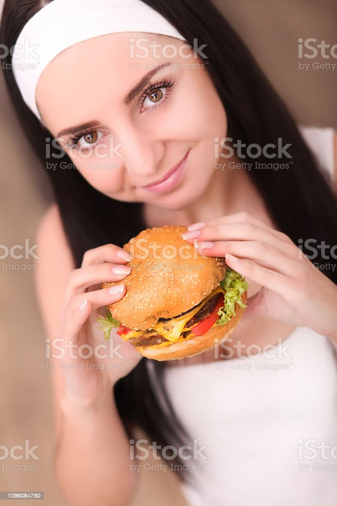 Young woman in a fine dining restaurant eat a hamburger, she behaves...
