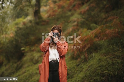 A young woman in a forest in autumn, taking pictures with a vintage camera