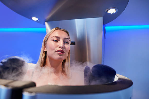 Young woman in a full body cryotherapy cabinet Young woman in a full body cryotherapy cabinet at cosmetology clinic. She is receiving skin treatment using cold nitrogen vapors. cryotherapy stock pictures, royalty-free photos & images