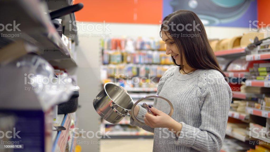 Junge Frau im Hause Warenspeicher wählt einen Topf – Foto