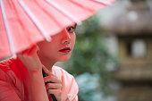 赤い日本の傘を持つ着物を着た若い女性