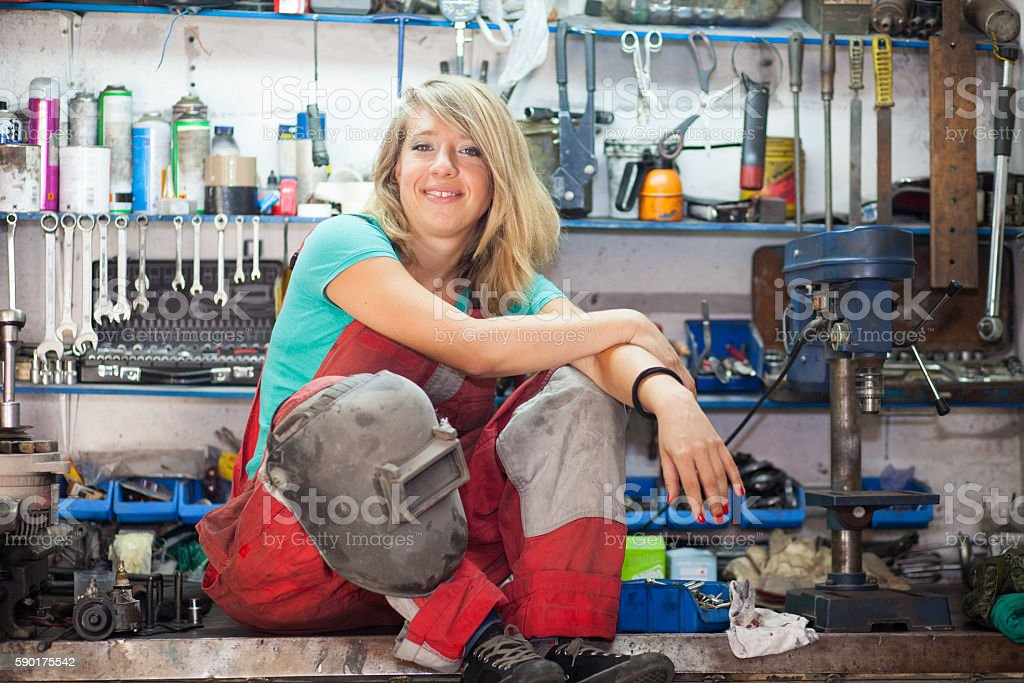young woman in a mechanic shop stock photo