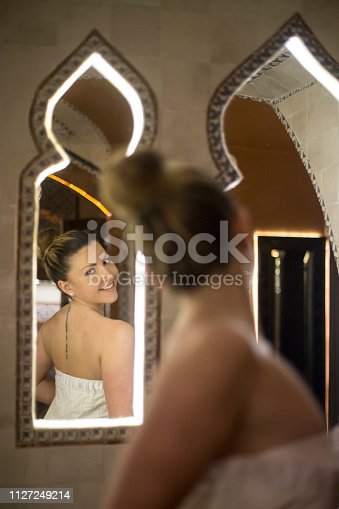Young woman in a oriental steam sauna - Turkish bath or hammam. About 25 years old, smiling Caucasian blonde.