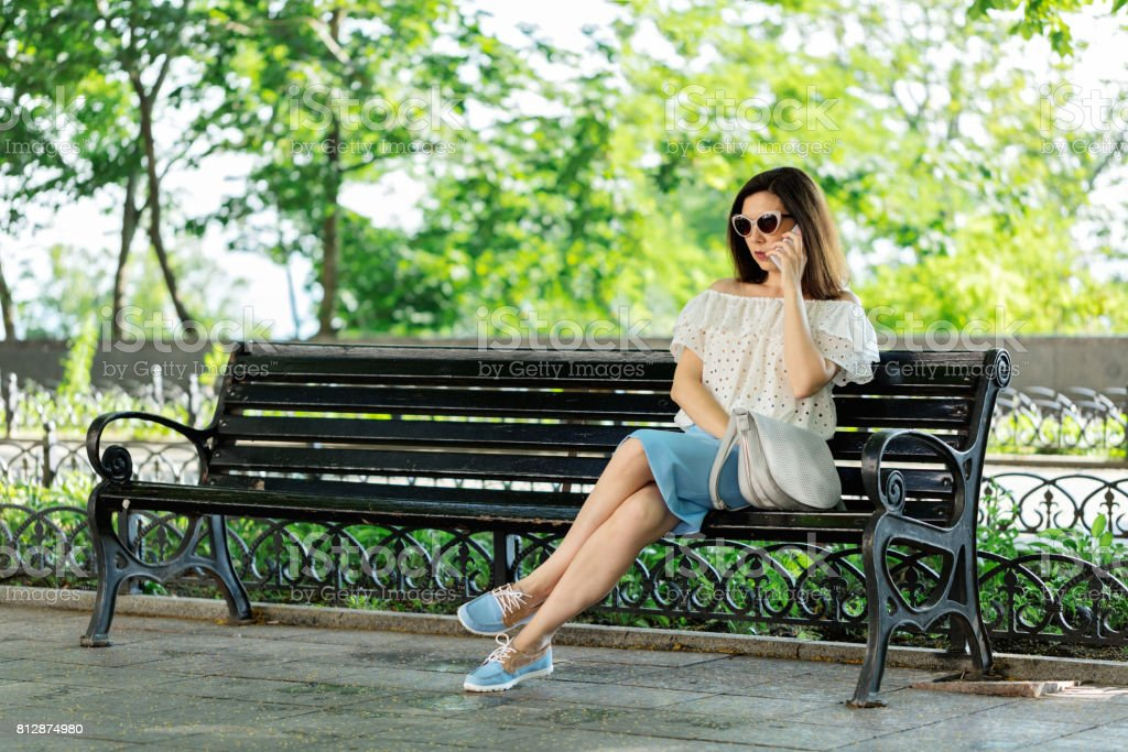 Young woman in a park in a white blouse and blue skirt is sitting on a bench and talking on a mobile phone. stock photo