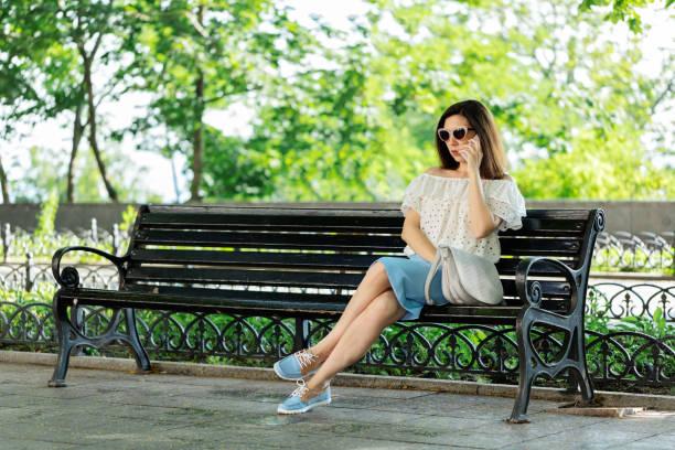 junge frau in einem park in eine weiße bluse und blauer rock ist auf einer bank sitzen und telefonieren mit einem handy. - rüschenbluse stock-fotos und bilder