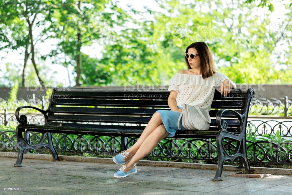 Young woman in a park in a white blouse and blue skirt is sitting on a bench. stock photo