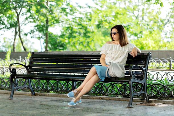 junge frau in einem park in eine weiße bluse und blauer rock sitzt auf einer bank. - rüschenbluse stock-fotos und bilder