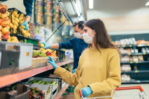 junge Frau in einer Schutzmaske kauft Äpfel – Foto