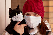 A young woman in a protective mask holds a masked cat in her arms. Conscious citizen in the fight against the epidemic of coronavirus