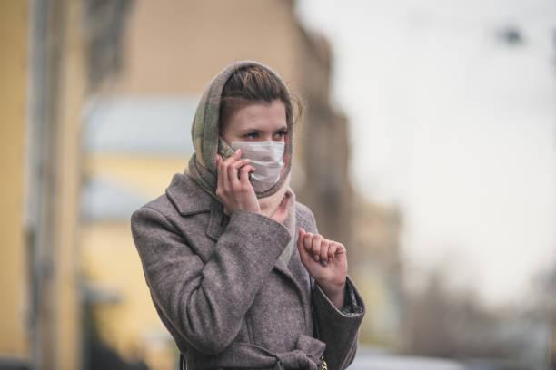Jovem com máscara de proteção falando em um smartphone na rua - foto de acervo