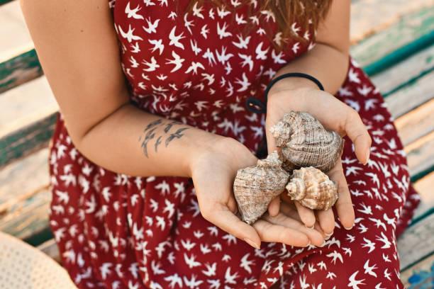 junge frau in einem roten kleid mit einem tattoo hält drei schöne muscheln - shell tattoos stock-fotos und bilder