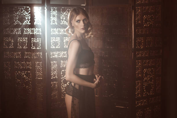 Young woman in a retro lace lingerue posing against wooden carved screen stock photo