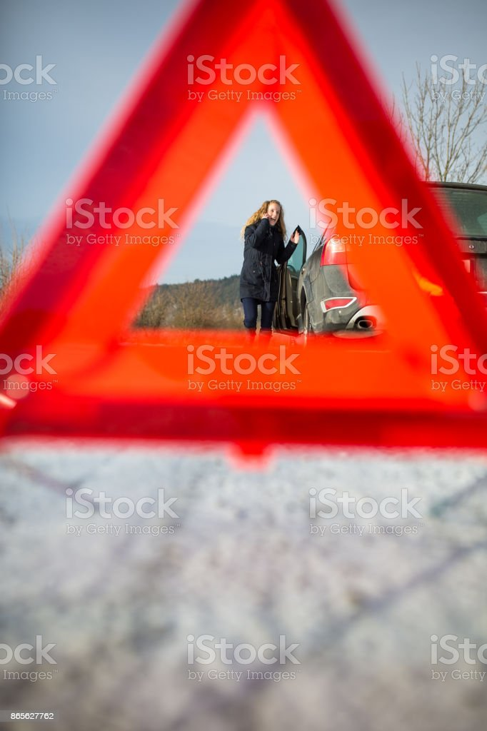 Young woman in a road distress situation - setting up a warning triangle and calling for assistance stock photo