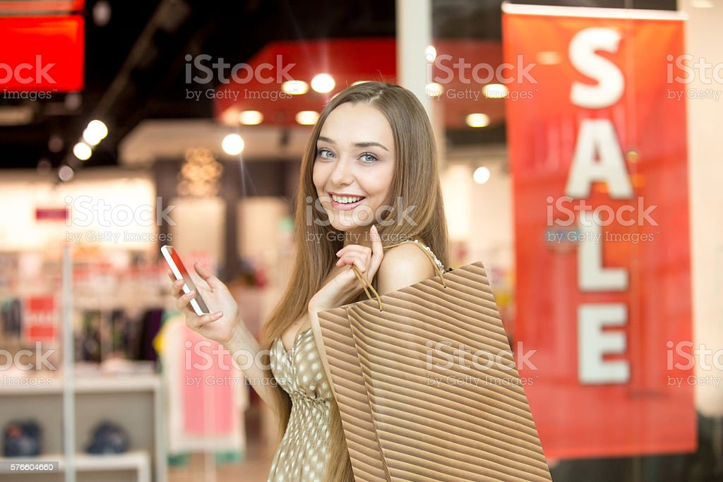 Young woman in a shopping centre holding a phone smiling стоковое фото