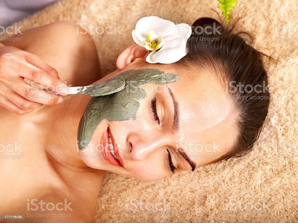 A young woman in a spa receiving a clay face mask royalty-free stock photo